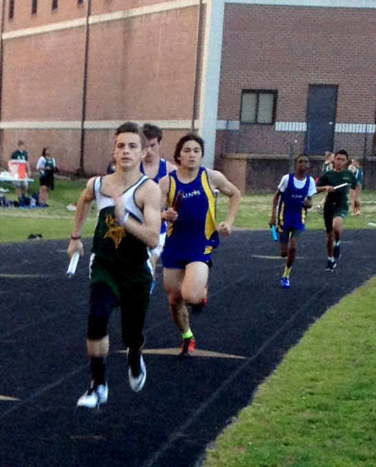 Freshman Joey Creed rolls during the first leg of boys varsity 4x400 relay